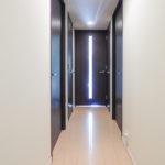玄関からリビングを見た廊下。ドアは落ち着いた雰囲気の色合いが採用されています。